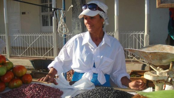 A farmer selling products at the Placetas fair: black and red beans, tomatoes, corn cobs