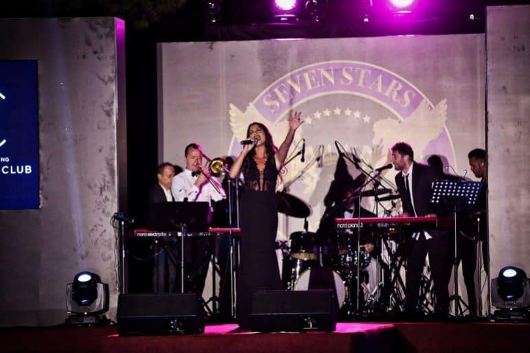 Nina Lotsari on stage performing for the event Dressed by Talented Designer Anna Veneti